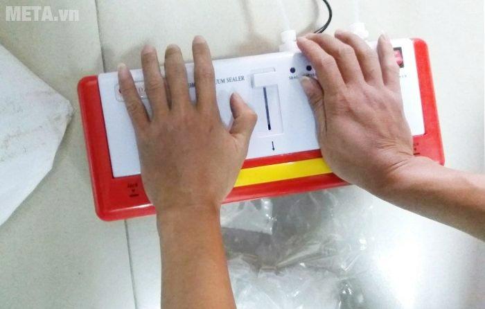 Nhấn 2 tay vào thanh màu vàng trên máy hút chân không DZ300B để hàn miệng túi.
