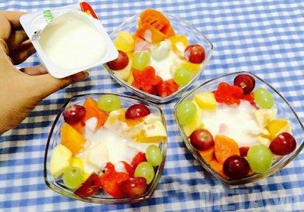 Cho hoa quả và sữa chua vào cốc hoặc bát rồi trộn đều