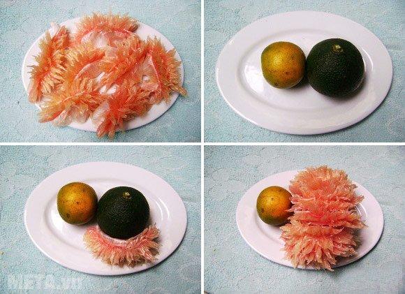 Lấy tăm gắn quả cam và quả quýt vào nhau, rồi gắn thêm múi bưởi đã tẽ lên quả cam