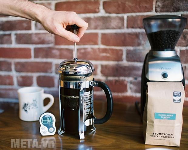 Tiến hành nén piston để tách bã cà phê và nước cà phê