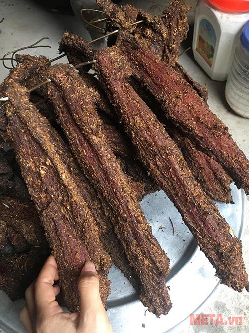 Xiên thịt vào móc sắt và đem đi hun khói 2 ngày