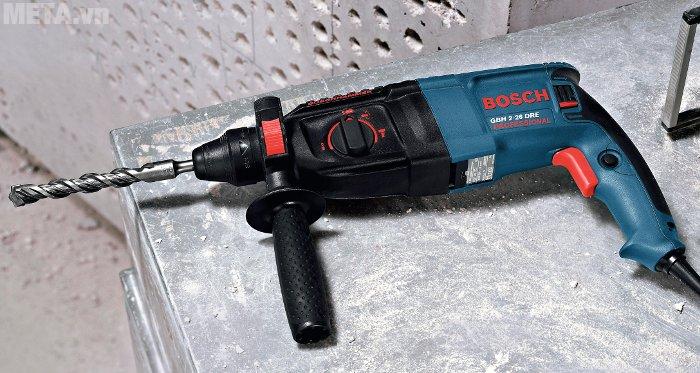 Bosch GBH 2-26 DRE đi kèm tay cầm phụ, thước đo độ sâu giúp khoan bê tông, tường, gỗ chính xác.